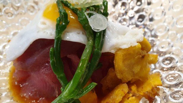 Tartar de atún, huevo de codorniz, patacones, salicornia y salsa de ajíes.